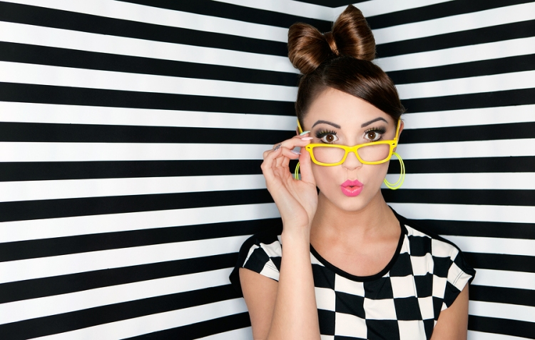 Attractive surprised young woman wearing glasses on checkered ba
