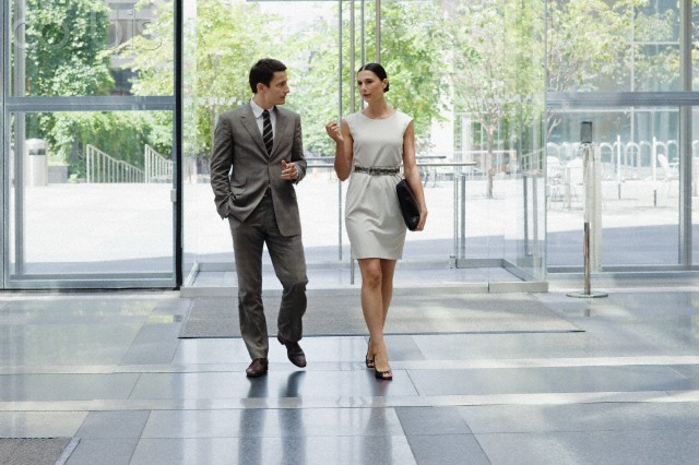 Business man and business woman walking in office lobby